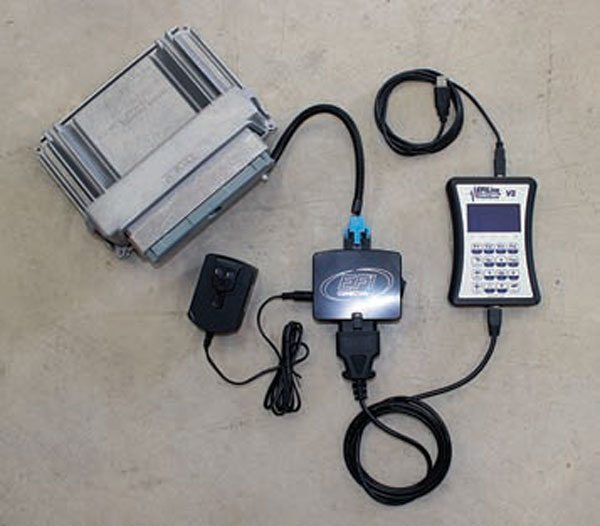 This is an example of an OBD-II bench-top programming solution. The PCM (top left) receives power and data communication through the switch assembly (middle) and can be reprogrammed with a laptop or desktop through a programming interface cable (right).