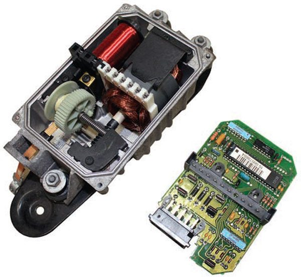 This 1996-newer GM cruise module assembly contains a circuit board for processing cruise control logic, an internal motor to operate a worm-driven gear, and a short braided strap to pull the throttle cable. This cruise control module uses PCM data to control the movement of the throttle cable when cruise control is active.