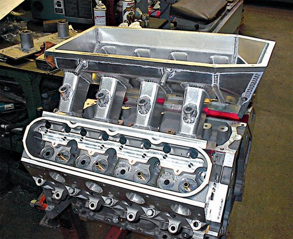 RaceKrafters built this custom intake manifold from aluminum sheet metal for a  440-ci naturally aspirated LSX (drag race only). This particular engine has All Pro LSW-2 heads and an operating range of 5,500 to 8,500 rpm. It is capped off with a lid and custom-CNC'd 125-mm throttle body. The unique port configuration, high-RPM range, and hood clearance limitations necessitated the custom manifold. Bob Wise of RaceKrafters says experience is crucial for knowing what runner shapes work, and the cross-section area and runner taper are critical for a well-designed manifold. He also added that port velocity in the head can be heavily influenced by runner shape and length, so much so that the manifold design is sometimes used to compensate for weak cylinders. (Photo Courtesy RaceKrafters)