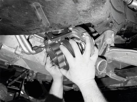 With the exhaust manifolds and their oxygen sensors in place, the first turbocharger is hoisted into position, sliding onto the mounting studs protruding from the exhaust manifold's mounting flange. In this photo, the passenger-side turbo is being installed.