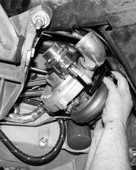 With the passenger-side turbo and its oil-feed line in place, the driver's-side turbo is installed and its oil-feed line attached.