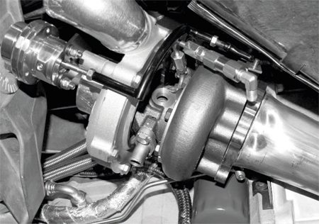 Next, the down tubes (the pipes that connect the exhaust outlet of the turbos to the vehicle's exhaust system) are installed, but not before they're test-fitted to ensure there are no interference issues with any of the other turbo system or chassis components.