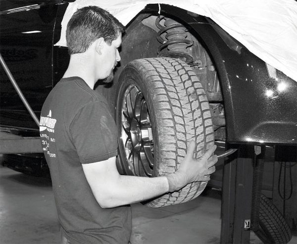 The supercharger kit's charge cooler requires removal of the front fascia. This starts with removal of the front tires to provide access to the myriad of fasteners (most of them plastic pushpin types) on the inside of the wheel well. There are also seemingly endless fasteners on the bottom of the fascia. The car used in this project is wrapped with protective coverings to prevent damage to the body. (See Chapter 4 for more information on fascia removal.)
