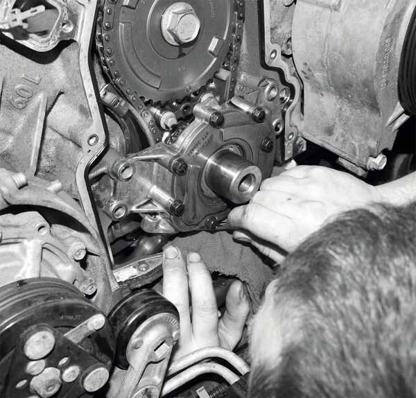 The oil pump has fasteners on the bottom edge that are very difficult to reach. Removing them requires a very slim wrench or ratcheting wrench. A rag placed beneath the pump helps prevent the bolts from falling into the engine if they were to slip from the wrench or your grasp.