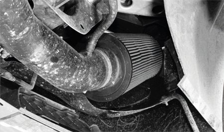 The air intake filters are mounted as far away from the heat of the turbo system as possible; in this case, at the far corners of the front bumper cover. Note the vacuum hose attached to the intake tube. It's part of a crankcase breather system.