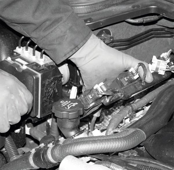 The procedural step with the engine involves the removal of the ignition coils. This is accomplished by disconnecting the plug wires from the spark plugs, disconnecting the coils' individual plug harnesses, unbolting the coil brackets from the valve covers, and lifting them out of the engine compartment. The coils are attached to the bracket, avoiding the need to remove them individually.