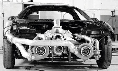 Here is a typical turbocharged race car under construction. The turbochargers were mounted up front on a fabricated brace, replacing the original bumper beam. Note how the turbos are fed by reversed, marinestyle headers, with the wastegates located before the turbochargers. The air outlets from the turbos merge into a single, large-diameter tube that is routed on the outside of the engine compartment (underneath the passenger-side front fender) to the passenger compartment, where it is cooled by a large, liquid-to-air intercooler. The cooled air charge is then fed through a hole in the firewall to a reversefacing inlet atop the intake manifold. This is not designed for street use, as all of the typical accessories found on a street car are eliminated to make room for the turbo system's tubing.