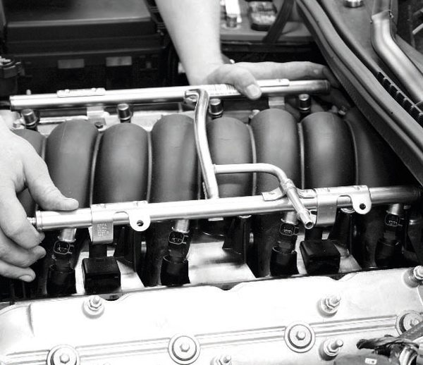 After routing the intercooler plumbing, attention turns to the fuel system. The kit's higher capacity, 60-pound/hour injectors were swapped onto the stock fuel rail. Then, the fuel rail was simply pushed back into place on the intake manifold.