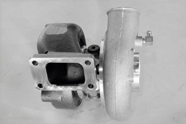 At its very basic, the turbo system channels exhaust gas via an exhaust manifold to the turbine side of the turbocharger. When the turbocharger is mounted directly to or very near the exhaust manifold, the manifold must be sufficiently thick and strong to withstand not only the heat of the turbo system, but also the reduction in temperature when the system is not under load or the engine is turned off. Thick cast-iron manifolds traditionally do the best job at this, because they resist warping.