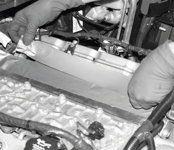 To prevent debris from falling into the engine during the intake manifold's removal and the supercharger's installation, duct tape is laid over the cylinder heads' intake ports. A shop vacuum should also be used on the top of the engine to remove any unseen debris. There's no such thing as too much caution in this area.