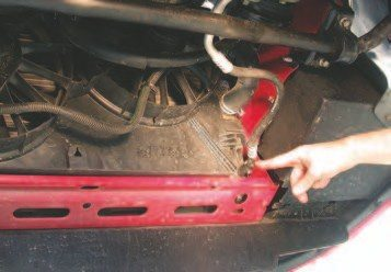 3. The coolant is the first fluid that needs to be drained from the vehicle when removing the engine. If the engine is going to be torn down once removed, now is also a good time to drain the oil. To drain the coolant, open the petcock at the bottom of the radiator on the passenger side of the vehicle (indicated by the finger in the picture). As a note, the Gen III V-8 uses a 50/50 mix of Dexcool and water.