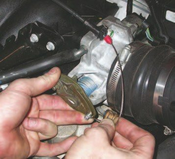7. Unloop the throttle cable from the throttle body arm and slide the cable end out the access slot to remove it from the anchor point.