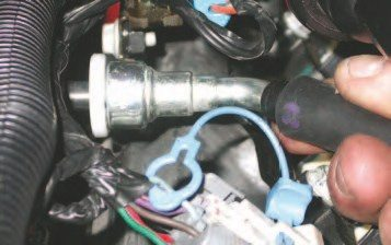 9. Pull the fuel line removal tool toward the vehicle feed line to release the tangs holding it in place. At the same time, push the feed line toward the removal tool. Once the tool is fully seated, you can remove the feed line from the manifold fitting — but be careful, as this line will probably be under pressure. Cover the joint with a rag and release it slowly to gently bleed off pressure.