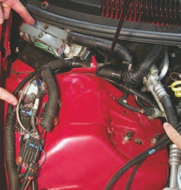 16. Here are all the plugs to unhook on the passenger side of the engine bay to remove the LS1 from an F-body: the two PCM plugs, all the smaller plugs in the foreground, and the plug on the right that is the A/C clutch WOT override. The two PCM connectors each have a 7-mm bolt to hold them in place. Use a socket to loosen them — the bolts are nested so they won't come out of the connectors. To remove the connectors, touch the vehicle to ground yourself, then carefully work the connectors out of the PCM. To remove the PCM, slide it out of its holder and carefully work it past the lower portion of the windshield and passenger-side shock tower.