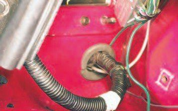 18. Here's a big timesaver. There are two wire bundles that run into the interior through a grommet on the lower portion of the firewall behind the passenger- side wheelhouse. You need to disconnect these to remove the engine. GM recommends pulling apart half the interior to get to these connectors. Many hot-rodders instead remove the firewall wiring grommet and carefully pull the wiring into the engine bay. There is just enough wire to get the connectors into the engine bay, allowing you to disconnect them without touching the interior. Be careful the plugs coming from the interior don't fall back through the firewall. You can avoid this by zip-tying them to the engine-bay wiring. To reinstall, plug the wiring connectors back together, feed the wiring back into the interior, and slit the grommet to get it back into the firewall.