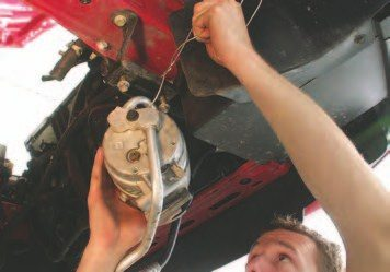 19. Now, the A/C compressor bolts can be removed. Start with the top two 15- mm bolts on the A/C bracket from the top of the engine bay. The bottom two 15-mm bolts are easier to remove from under the vehicle. Then swing the A/C compressor and adjoining hoses towards the front of the vehicle and hang the pump from the radiator core support with a coat hanger or zip ties so the hoses don't have to be unhooked from the vehicle. This way, you won't have to recharge the A/C system later.