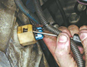 22. Lift the retention tang off the oil level sensor connector and pull it off the sensor.
