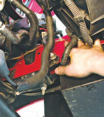 24. There are numerous ground straps tying the powertrain and vehicle together, like this one (finger pointing to it), and they all need to be disconnected before you remove the engine. Watch for them as you go through the removal process, as the ones you miss will be torn off when the lift goes up!