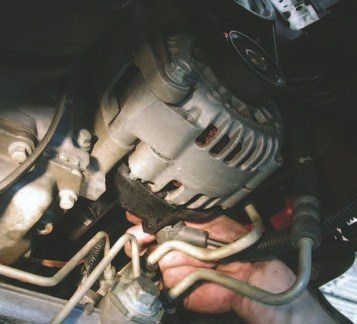 25. Working from underneath the front subframe and behind the alternator, use a 13-mm flex socket on a 10-inch ratchet extension to remove the constant power wire nut (in hand) that hooks up to the back of the alternator.