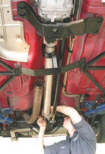 30. Now is the time to remove the driveshaft. Remove the U-joint bolt-on caps at the front of the rear end and slide the driveshaft forward slightly to release it from the pinion. If the rear end is hanging at full droop, getting enough clearance might be difficult. To get the driveshaft loose, you might need to remove the U-joint bearing caps for extra clearance. A good tip is to put the caps back on right away and use electrical tape to hold them in place while you work on the rest of the vehicle so the needle bearings don't fall out of the caps.