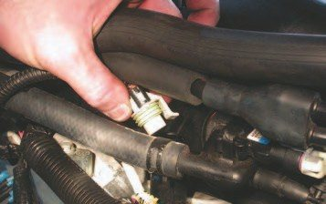 33. Disconnect the oil pressure sender at the back of the intake on top of the valley plate (in fingers). You also need to disconnect the hose plugged into the manifold pressure sender, located just below the finger in the picture.
