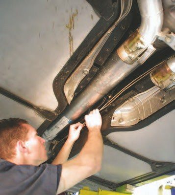 6. Remove the brake lines from their clips in the tunnel, as these lines will come down with the powertrain assembly.