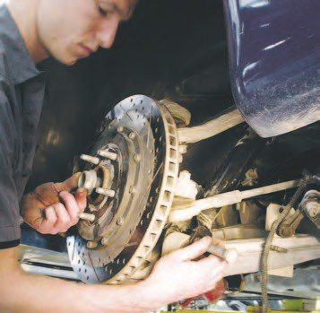 11. Next, you need to disassemble the rear suspension. To start, support the spindle upright with a stand. Then, remove the 24-mm nut/bolt combo holding the lower shock absorber on the lower control arm. Loosen the 18- mm nut holding the upper ball joint in place, rattle the tapered ball-joint shaft with an air hammer or take a 3- lb hammer and smack the upper control arm with slight spring pressure on it to release the ball joint. Then, get out a massive 1-5/16-inch socket and loosen the halfshaft nut in the upright.