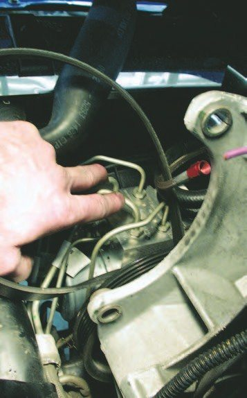 14. Back in the engine bay, remove the brake lines from the ABS control module that sits in front of the engine.