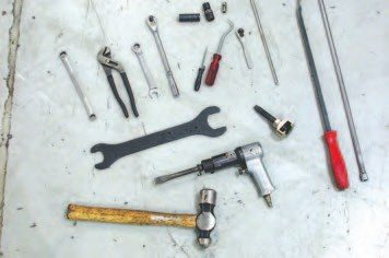 The tools required to do this job vary from the standard pliers, screwdrivers, and open-end wrenches to a custom pulley puller and radiator hook tool. The hammer and pry bar are used to persuade various components away from their homes.