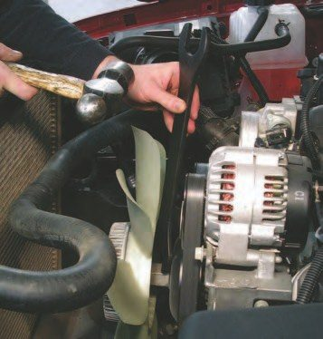 "6. Remove the fan next. Use a 36-mm wrench (Blue Point, PN YA9521) to twist the nut against the cranking rotation of the belt (the belt direction is different on the various front drives). Don't remove the accessory drive belt before doing this, as the belt will hold the water pump shaft in place while you loosen the fan nut. You should be able to remove the nut by hand, but if not, refer to the next photo for how to remove ""stuck"" fan nuts. Remove the lower shroud by taking it off its two resting tabs."