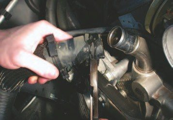 9. Use pliers to compress the spring clamp holding the upper radiator hose on the engine. If possible, compress the clip until it detents open to make reinstallation a snap (literally). Lift the hose to drain the coolant in the hose back into the radiator. As a note, these clamps are staked to the hoses, so they won't slide back and forth on the hose.