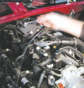 12. Take off the upper cover bracket on the intake manifold by removing the three 10-mm bolts. Reinstall the bolts in the intake after the cover bracket is off so you don't lose them.