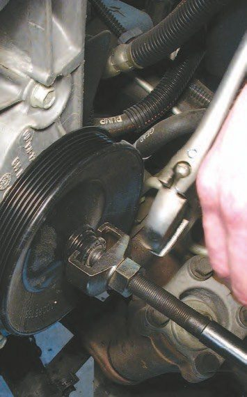 30. Remove the front accessory drive belt by relaxing the tensioner belt with a 15-mm wrench and pulling the belt off by hand.