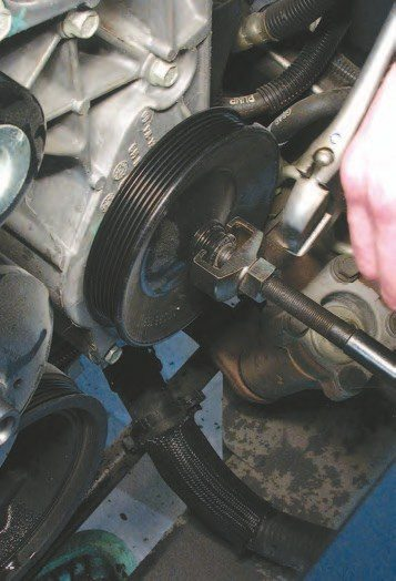31. Remove the power steering pulley to access the four bolts holding the pump onto the engine. This is done to keep the power steering system together — it's easier to remove the pump from the engine than it is to take the whole system apart and put it back together. Use a special puller tool (Snap-On, PN CJ117A) to pull it, and a special install tool (Snap-On, PN CJ113B101) to reinstall the pulley.