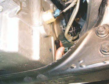 36. With the starter out, use a straight pick to depress the hidden tab on the oil-level wiring connector to remove it from the oil pan. While you're down there, remove the 10-mm bolt that's holding the harness on the front of the oil pan.