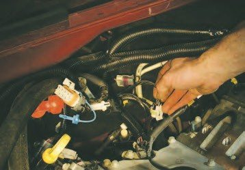 42. Before you separate the connector for the oil-pressure sender (shown) and knock sensors, push the wiring loom back towards the firewall. Remember to tape over the intake ports to prevent objects from falling into the engine. This engine was being completely rebuilt, so this precaution was not taken.