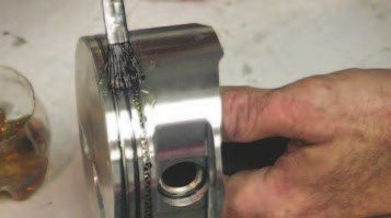 2. Wipe a very light amount of 30-weight oil on the rings and thrust faces of the piston.