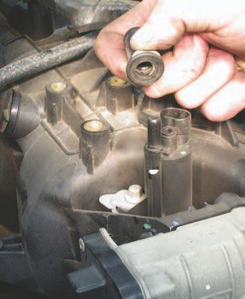 To remove the Air Injection Reaction (AIR) system tube (what many would call the EGR) on the intake manifold behind the throttle body, you'll need to depress the gray sliding tab into the connector body and wiggle the connector to the side of the mounting tube while lightly pulling on the AIR tube. Once it's off, look at how the offset clip moves over when you squeeze it to release the tube from the intake.