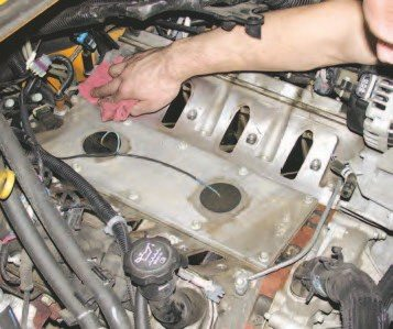 With the intake removed, carefully scrape off the mounting surface of the intake, using a vacuum to suck away any debris before it can fall into the intake. Wipe this surface down with solvent, allow it to dry, and cover it with tape until just before the supercharger/ intake manifold combo is installed.