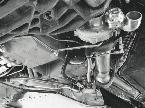 This photo illustrates the complexities of designing and/or installing a turbo system on a street vehicle that retains all of the other factory controls, chassis and suspension elements. Note the various hard lines and hoses that snake in and out of the turbocharger (and mirrored on the opposite side of the engine compartment). Developing such a system is time intensive, and so is installation. Also, slight vehicle changes between model years can require substantial reengineering. That's why there aren't as many bolt-on turbo kits on the market, compared to blower kits.