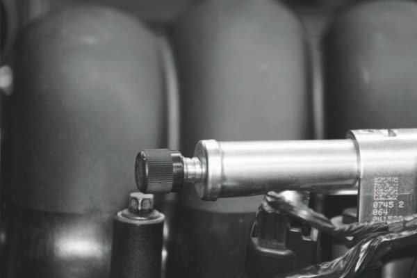 Fuel-pressure relief is accomplished by accessing the Schrader valve located behind this black cap on the driver's-side fuel rail. The cap simply unscrews like the air valve on a tire.