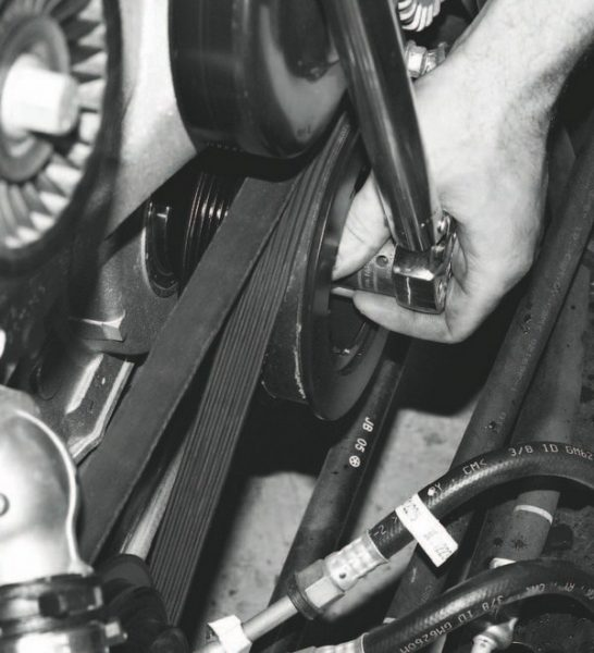 The final torque angle of the damper bolt is an extremely high torque spec (approximately the equivalent of 250 ft-lbs) and requires considerable leverage to hold the flywheel or flexplate to prevent the crankshaft from turning. Specialized tools are available for this job, but one of the most effective methods is to use a serpentine belt wrapped around the balancer and air-conditioning pulley, which holds the damper in place.