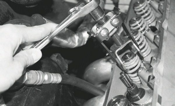 With the air line connected at the spark plug hole, the spring tool is lowered onto the top of the spring. A ratchet is used to compress the spring until the retainer and keeper can be removed, freeing the spring. Extreme care must be taken since the spring is under tremendous pressure and could cause an injury or even damage if it breaks loose from the tool.
