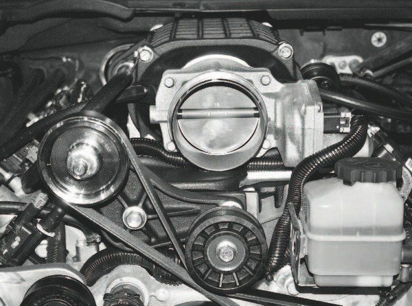 This photo shows the throttle body installed on the supercharger, as well as its lengthened wiring harness plugged into it. It also shows the myriad of other hoses, connectors, and fasteners re-attached to the engine and/or supercharger/ manifold assembly. Despite their common LS engine architecture, different vehicles have different connections, sensors, and other hardware. Again, the manufacturer's assembly manual should be followed closely to ensure all of the connections have been made. A few items to check include the Idle Air Temperature (IAT) sensor, EVAP lines (which may require modification or replacement on some vehicles), purge solenoid, vacuum hoses, and MAP sensor/wiring harness.