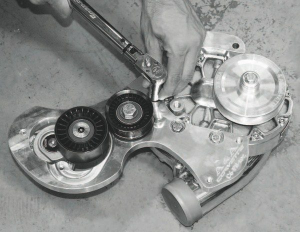 The front part of the bracket is then mounted to the supercharger compressor. The bracket contains a tensioner that replaces the factory unit, which was removed to make room for the supercharger.