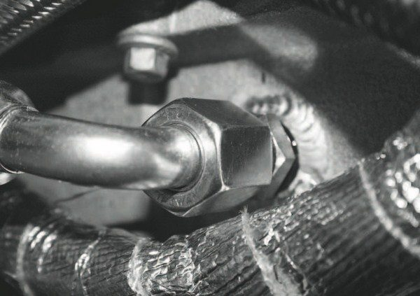 One of the other pre-installation procedures involves prepping the engine for the oiling requirements of the turbos. That involves swapping the stock oil cooler for an aftermarket model, fitting a scavenge pump to pull returned oil from the low-mounted turbos and adding a feed line (seen here) to the oil pan that sends the circulated oil back into the pan.