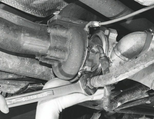 The turbo system includes a pair of Garrett GT28R watercooled, ball-bearing turbochargers. Seen here is one of the turbochargers mounted to an exhaust extension that bridges between the turbo and exhaust manifold. Because of this arrangement, the turbocharger is located at the bottom of the engine compartment, in the approximate area of the original catalytic converter. The lower mounting position not only reduces underhood heat, but the thermal barrier for the converter also provides heat shielding.