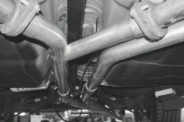 At the top of this photo, the Y-pipe illustrates the merge of the left- and right-hand exhaust outlets and its flow rearward to the turbocharger. The separate tube at the right is the flow tube carrying the boosted air charge to the intercooler and, after that, to the engine. The length of the tubes and their distance from the exhaust manifolds provide a passive intercooling effect.
