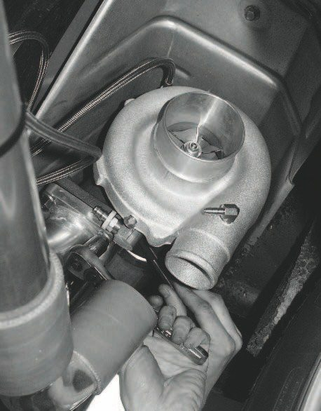 Looking up at the chassis, with the left-rear tire on the right side of the photo, you can see STS' mounting location for the turbocharger. It's the location of the original muffler, which is eliminated with this system (although that is not true for all STS kits). A benefit of this mounting position is the factory heat shield that was originally designed for the muffler.