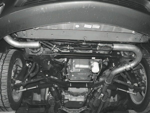 This view looking up at the front of the car shows the inlet pipe from the turbo coming in from the right, with the outlet to the engine intake on the left. What's missing in between is the heat exchanger for the intercooler.